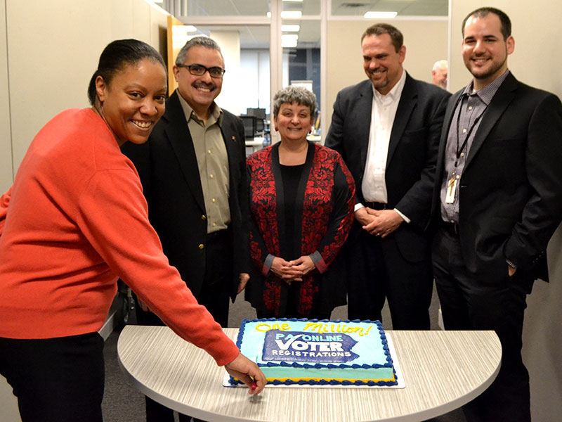 Group of election staff cutting a cake celebrating the 1 millionth registration.